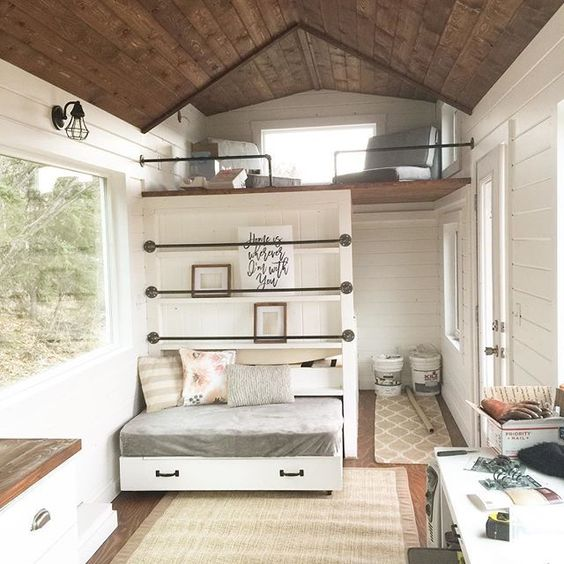 You see a bed in a drawer in a tiny house