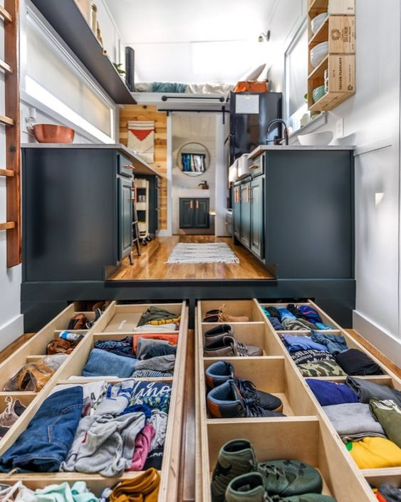 You see a drawer placed under the floor of a tiny house.