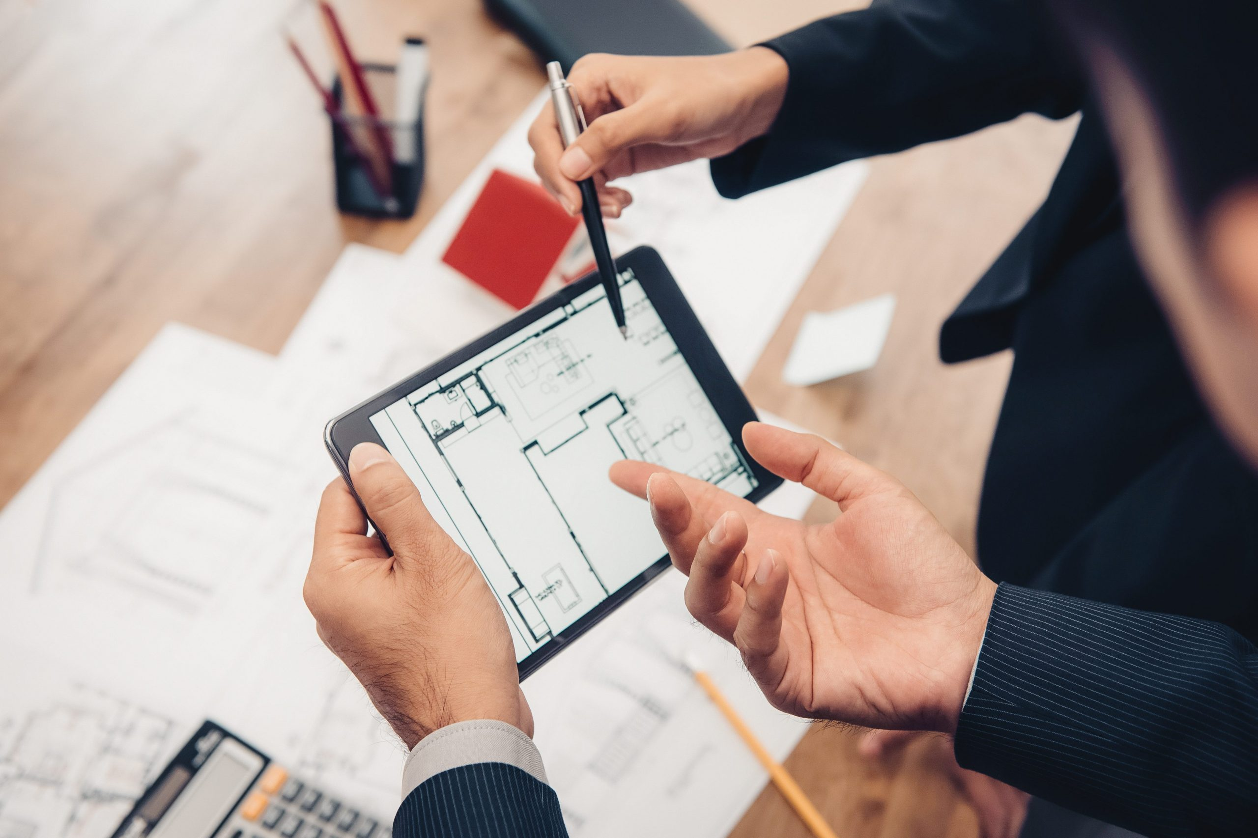 Real estate agent with client or architect team discussing a housing model and its blueprints digitally using a tablet computer