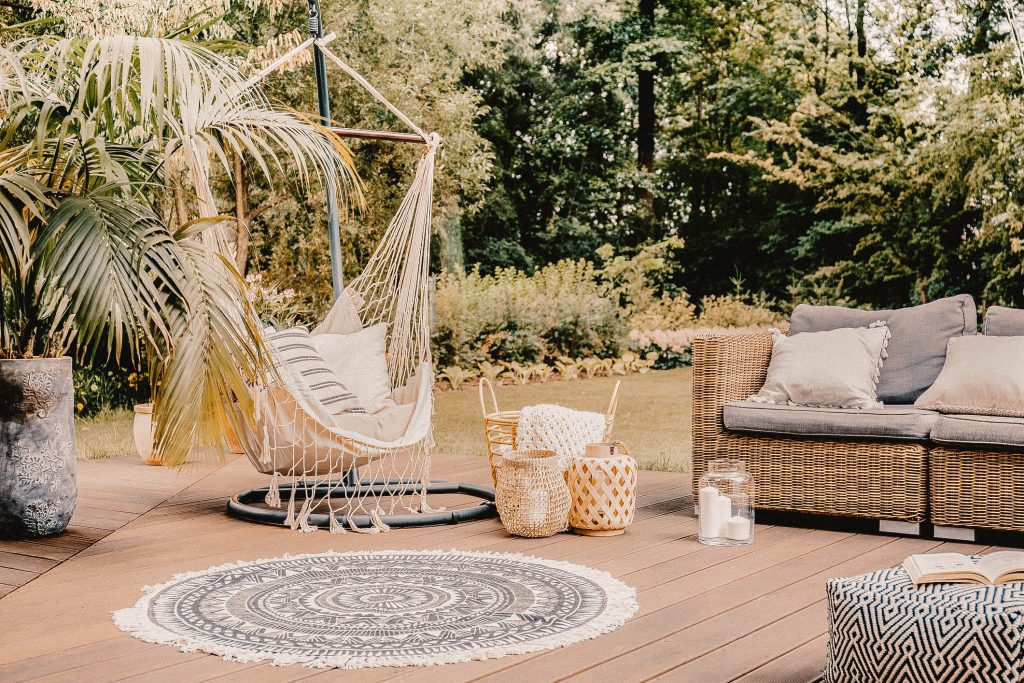 Hanging chair on a deck with a couch