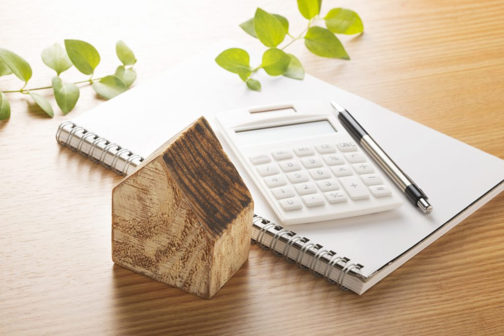 Wooden house and calculator to illustrate the planification of a home addition.